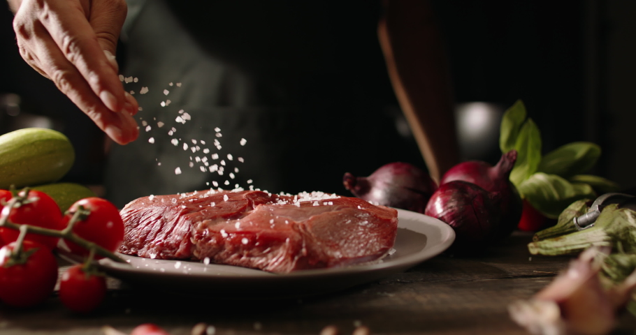 Chef applying grained salt on raw piece of steak. Cooker preparing meat on professional kitchen table with various vegetables 4k footage | Shutterstock HD Video #1062736174
