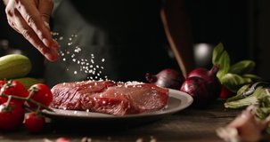 Chef applying grained salt on raw piece of steak. Cooker preparing meat on professional kitchen table with various vegetables 4k footage