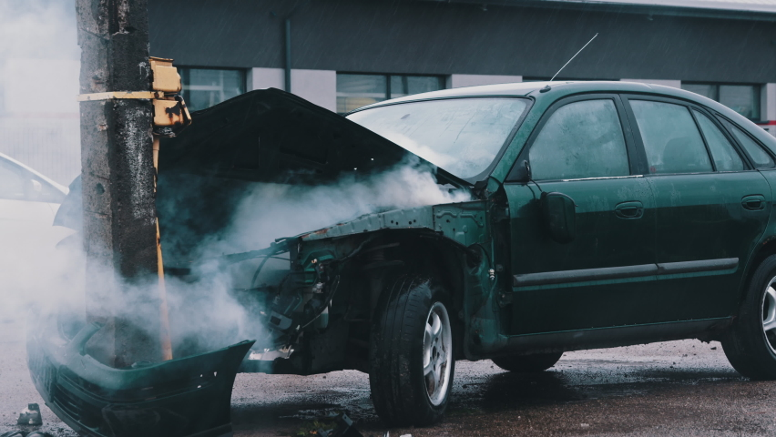 Smoke from wrecked car with fire engine in the background. Car accident. High quality 4k footage