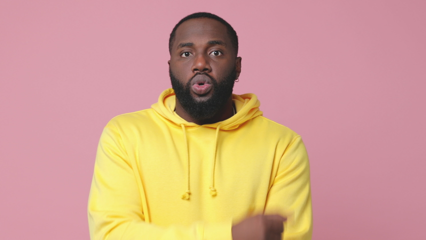 Strong laughing young african american man 20s wearing yellow hoodie isolated on pastel pink color background studio. People lifestyle concept. Showing pointing on biceps muscles doing winner gesture | Shutterstock HD Video #1062752995
