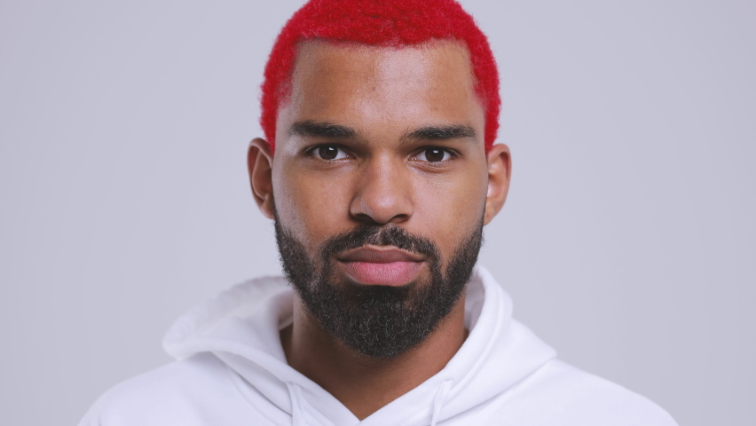 Close up of shocked amazed young bearded black african american man with funky red hair 20s in streetwear hoodie look aside camera say wow isolated on white background studio. People lifestyle concept | Shutterstock HD Video #1062753055