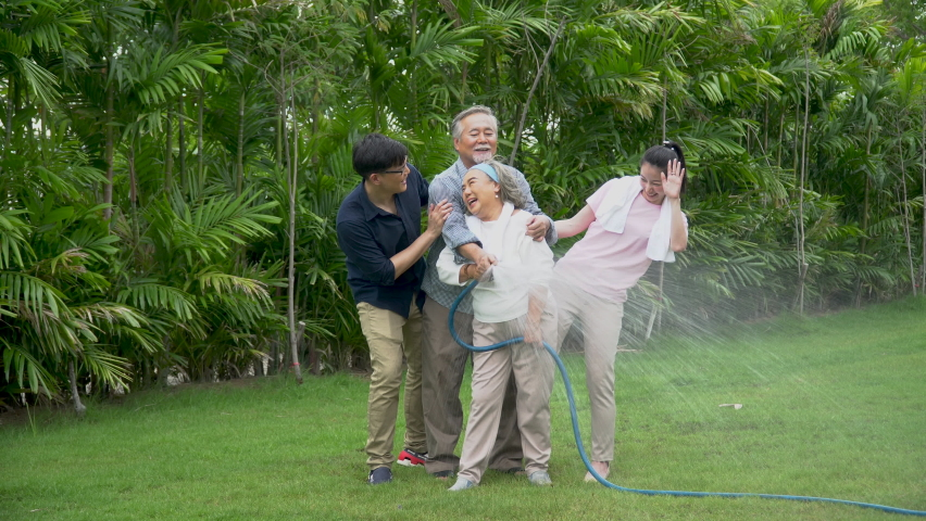 Happy asian family watering the plants  in the front lawn at home  Spend time together lifestyle in garden