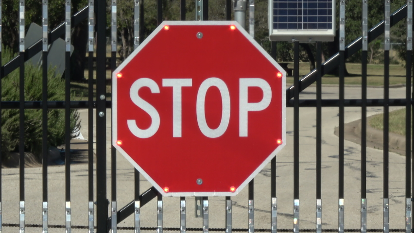 Large flashing solar powered stop sign at gate // 4K Royalty-Free Stock Footage #1062763609