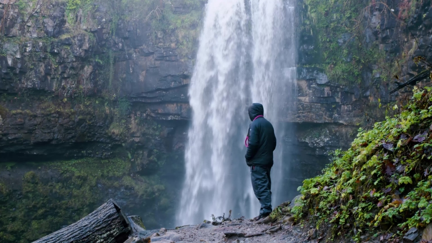 Male stood infront of water fall at henrhyd falls during the winter. South Wales uk. also known for the iconic film batman
