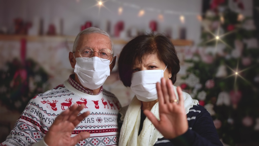 A couple of mature woman and man with surgical mask standing together, looking at camera at Christmas time or at New Year's eve at home. Royalty-Free Stock Footage #1062768670