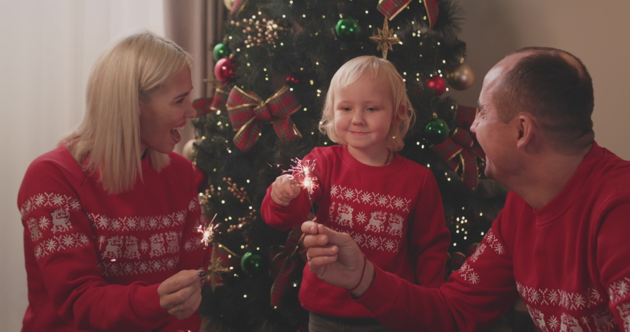 Happy parents celebrating Christmas together with adorable three-year-old son near decorated fir tree, holding lighted sparklers, having fun. Royalty-Free Stock Footage #1062769465
