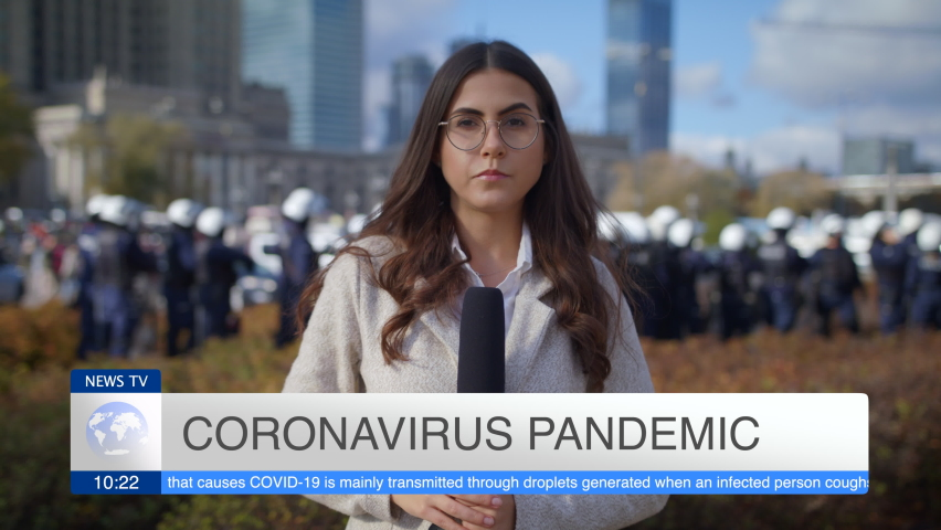 Caucasian Young Woman Journalist Looking At Camera And Presenting Breaking News TV About Coronavirus Pandemic On Street Outdoors Lot Of People Police In Background Pandemic City Protest And March