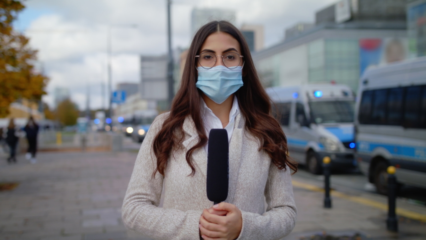 Caucasian Confident Young Woman Journalist In Protective Mask With Microphone Presenting Breaking News TV About Coronavirus Pandemic On Street Outdoors Cars On Signals Police In Background