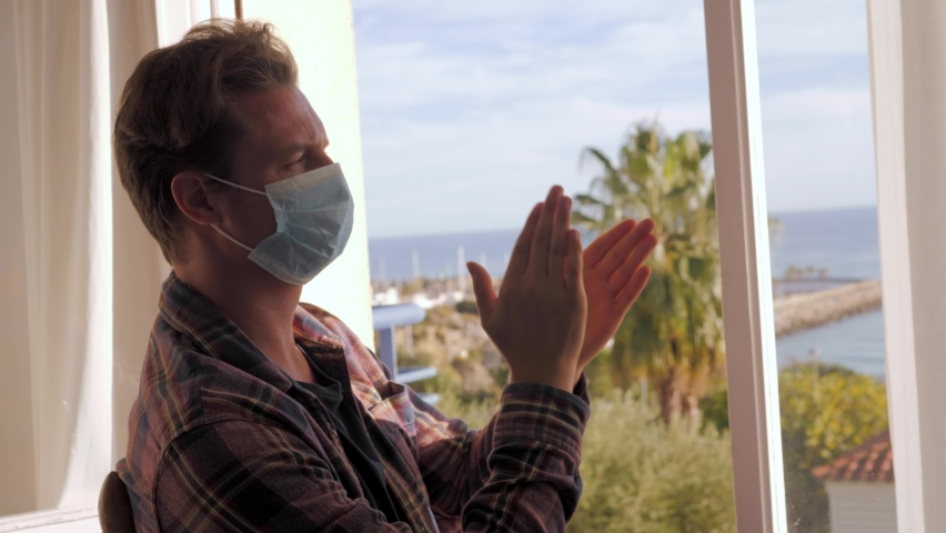 Middle aged handsome man on lockdown with medical mask clapping aplause on balcony to support doctors and medical workers with fight against covid 19 coronavirus.