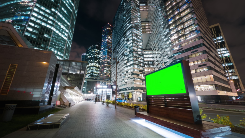 Modern billboard with a green screen on a busy street of the big city in the night. Road traffic and gigantic skyscrapers glittering with neon lights and pedestrians passing by in motion timelapse. | Shutterstock HD Video #1062778360