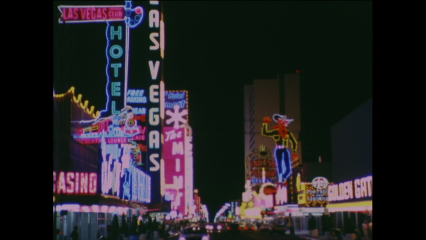 1960s: Film slate. Neon sign for the Sands. Neon signs from casinos, restaurants down strip in Las Vegas.