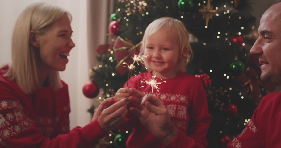 Happy married couple celebrating Christmas together with adorable three-year-old son near decorated fir tree, holding lighted sparklers, having fun. Royalty-Free Stock Footage #1062804463