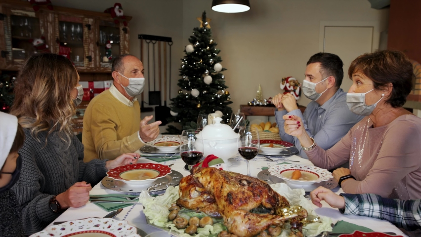 Happy family members wearing surgical masks at the Christmas Thanksgiving table at home in the year of the Covid-19 Pandemic. Grandfather proposing a toast. New rules, new health regulations. Royalty-Free Stock Footage #1062809896