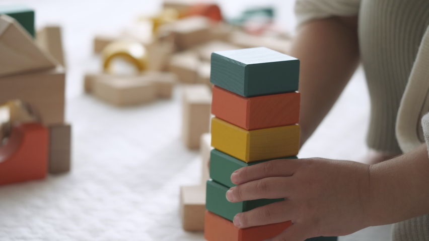 Close-up of child's hand playing with wooden blocks on the white floor mat at home. 2 years old little toddler baby girl. Collapses when trying to stack high. Messy building blocks background Royalty-Free Stock Footage #1062810613