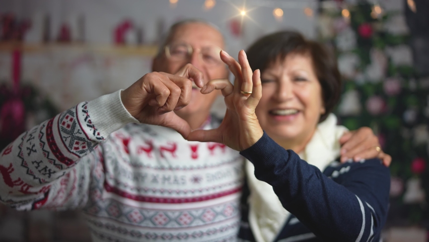 A beautiful mature caucasian couple making a video call on Christmas day. Grandparents holding a smartphone to say hello to her family away from home and showing them a heart made with fingers. Royalty-Free Stock Footage #1062812467