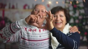 A beautiful mature caucasian couple making a video call on Christmas day. Grandparents holding a smartphone to say hello to her family away from home and showing them a heart made with fingers.