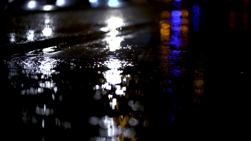 Blue lights of emergency vehicle reflecting from wet ground during rainstorm in Munich. Illuminated city during dark rainy night