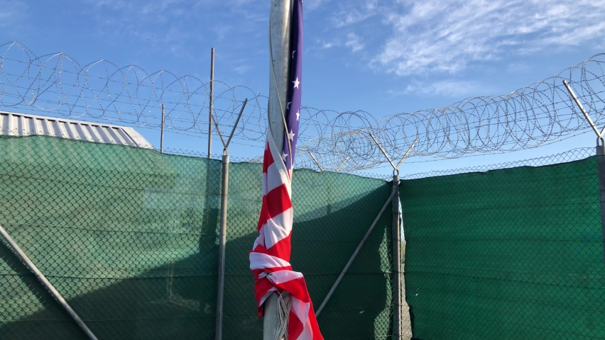 The United States stars and stripes banner against blue sky as banner for a fenced american facility with grate, razor wire and barb wire barriers. protected base area or confinement concept shot.