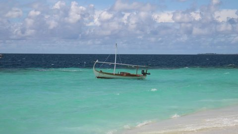 The anchored boat floats in vivid blue ocean water with waves crashing around.