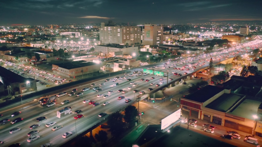 Busy traffic on I-10 freeway in downtown Los Angeles at night. Aerial city skyline panorama view. 4K UHD.