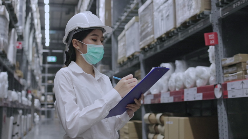Warehouse worker or Asian woman Happy labor wear medical mask to prevent Coronavirus and PM2.5 dust. Wear hardhat for protection while working in the transportation industry. Concept key worker Royalty-Free Stock Footage #1062820696