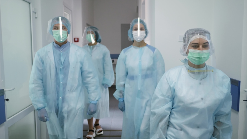 Team of Doctors in Protective Suits. Medical Workers Masked Walk Down the Corridor of a Modern Hospital. Fighting Covid-2019. Royalty-Free Stock Footage #1062822628
