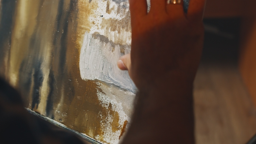 Close-up shot of the canvas has been painting by artist hand with oil paint. Emotional oil painting, art therapy, fine art concept
