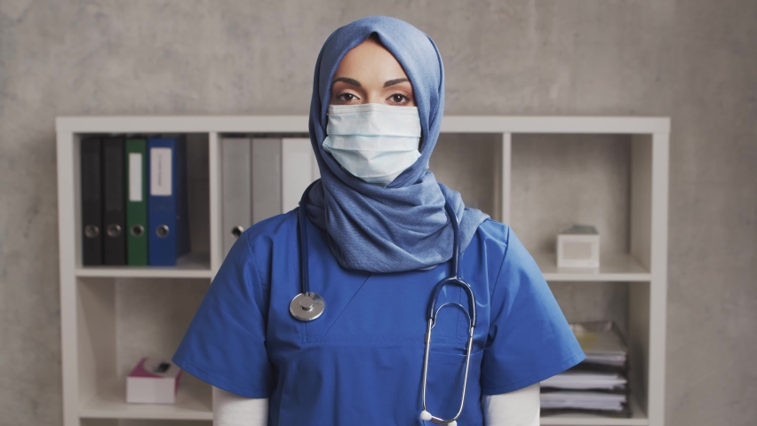 Professional Muslim medical doctor works in hospital office. Young and attractive Middle Eastern female physician in protective mask. Medical concept. Royalty-Free Stock Footage #1062828448