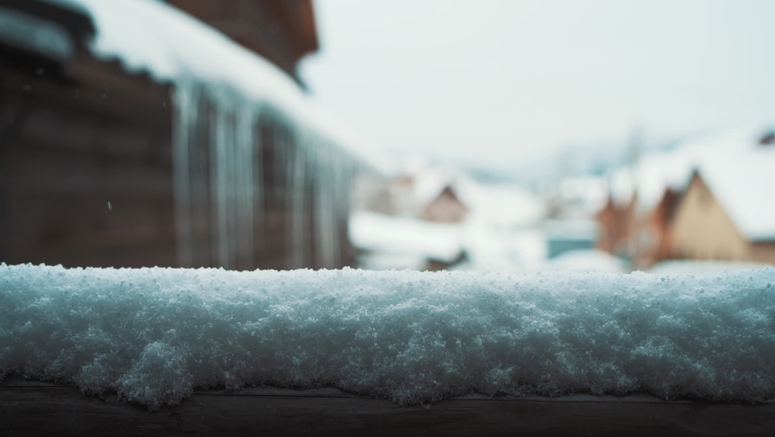 Snowfall and snowdrift on wooden handrail in foreground with falling snowflakes in the resort in mountains. Blurred background with houses and snow. Winter Christmas theme. Slow motion, Full HD video