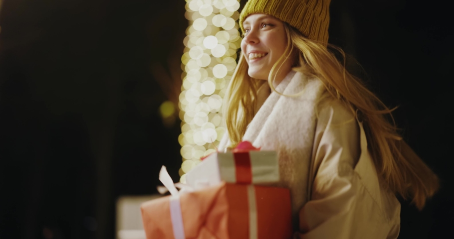 Young caucasian blonde woman holding plenty of presents running on city streets public park under lights hurrying to spend christmas holiday time boxing day.