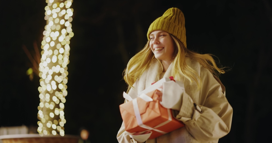 Young blonde woman holding holiday present running on the street of public city park under lights hurrying for boxing day christmas time birthday party.