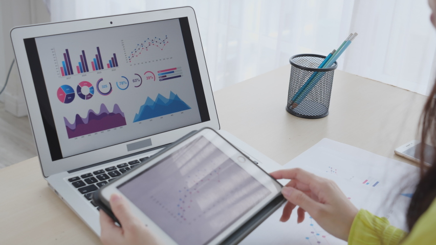 Young asian business woman working on laptop computer and looking graph and chart of report for profit on tablet at home office, businesswoman looking investment and income, data of infographic. Royalty-Free Stock Footage #1062839797