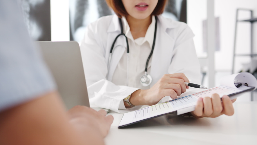 Young Asia female doctor in white medical uniform using clipboard is delivering great news talk discuss results or symptoms with male patient sitting at desk in health clinic or hospital office. Royalty-Free Stock Footage #1062848251