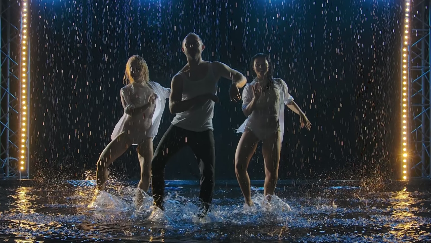 Two women and a man dancing a passionate dance of salsa in raindrops on a dark studio background. Professional dancers practice Latino in a smoky studio on the surface of the water. Slow motion.