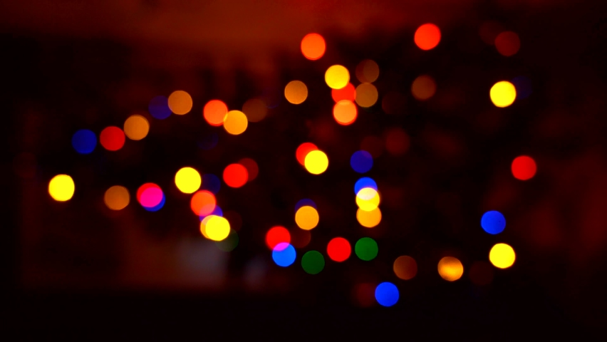 Blurred silhouette of Christmas tree with lights glowing Out of focus. Vertical 4k video. Christmas tree in interior with defocused lights. Christmas blur background. Light bokeh from Xmas tree.  | Shutterstock HD Video #1062860455