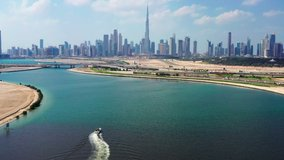 Aerial view of Burj Khalifa and Dubai skyline with yacht sailing in lake towards Downtown Dubai