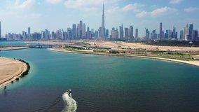 Aerial view of Burj Khalifa and Dubai skyline with yacht sailing in lake towards Downtown Dubai