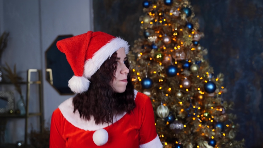 Young woman in Santa Claus costume dancing on background of Christmas tree. Happy female resting and celebrating Christmas at home. Concept of holidays and good mood. Royalty-Free Stock Footage #1062864085