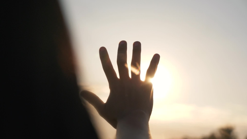 Silhouette of a happy dreaming girl pulls her hand to the sun. Religion helping hand. Happy girl pulls her hand. Prayer in religion. Silhouette of a hand in the sun. Happy girl silhouette at sunset Royalty-Free Stock Footage #1062867658