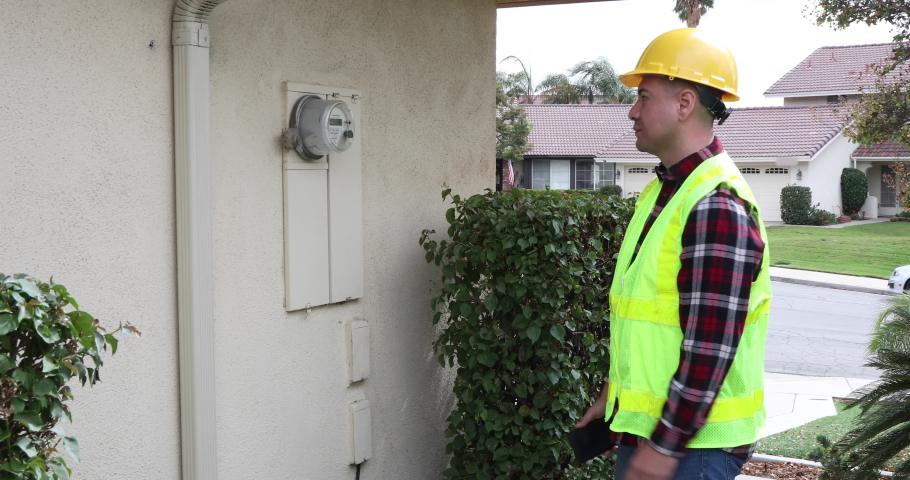 Man installs digital electric smart meter at a home. Royalty-Free Stock Footage #1062869356
