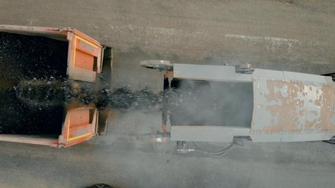 Paver pours powdered cover into truck. Close up of removing old layer of asphalt with milling and grinding machine. Road construction works. Construction machinery performs energy intensive heavy work