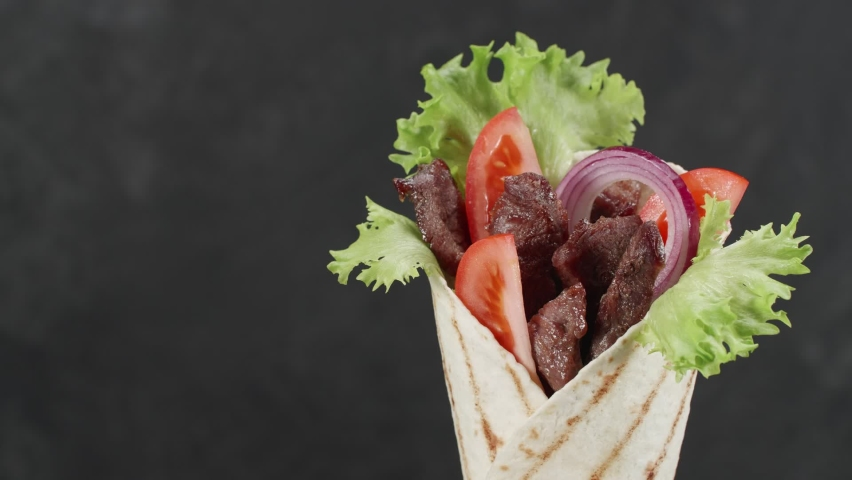 Shawarma or doner kebab moves on an black background. Shawarma is made with tortilla, beef, tomato, onion and lettuce.   Shutterstock HD Video #1062880300