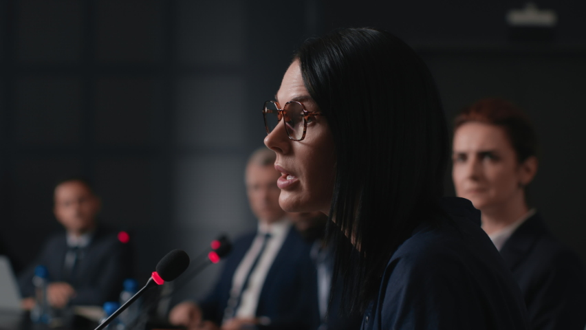 Speech of political speaker at meeting room of modern business center. Adult woman in suit explains leadership idea indoors of convention hall. Expert group works together at economic debate closeup Royalty-Free Stock Footage #1062880429