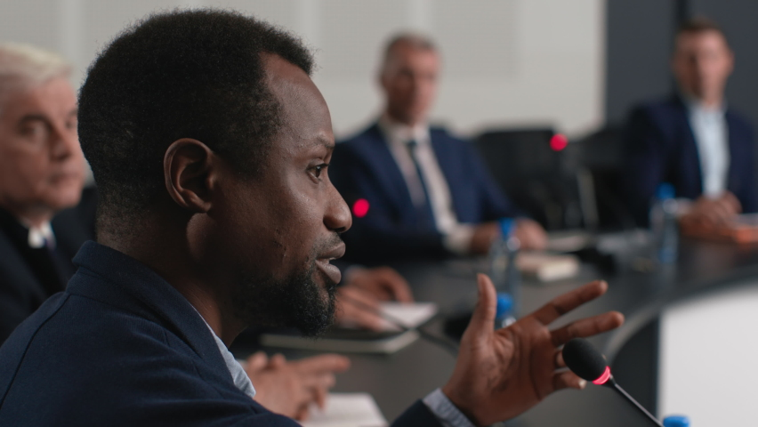 Speech of political speaker at meeting room of modern business center. Adult black man in suit explains leadership idea indoor of convention hall. Expert diverse group works at economic debate closeup Royalty-Free Stock Footage #1062880447