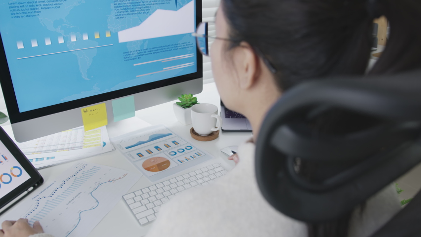 Over head shoulder back view of young attractive asian woman busy work multiple screen computer and smart tablet on table desk at home in concept freelance data analyst, data scientist for business. Royalty-Free Stock Footage #1062883198