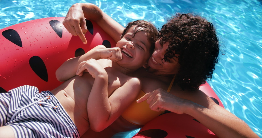 Mother tickling son in swim ring in a pool