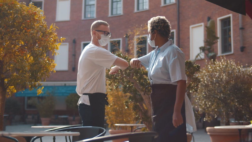 Diverse waiters in safety mask greeting touching elbows standing outdoors cafe. Coffee shop owners bumping elbow wearing apron and protective mask standing on terrace