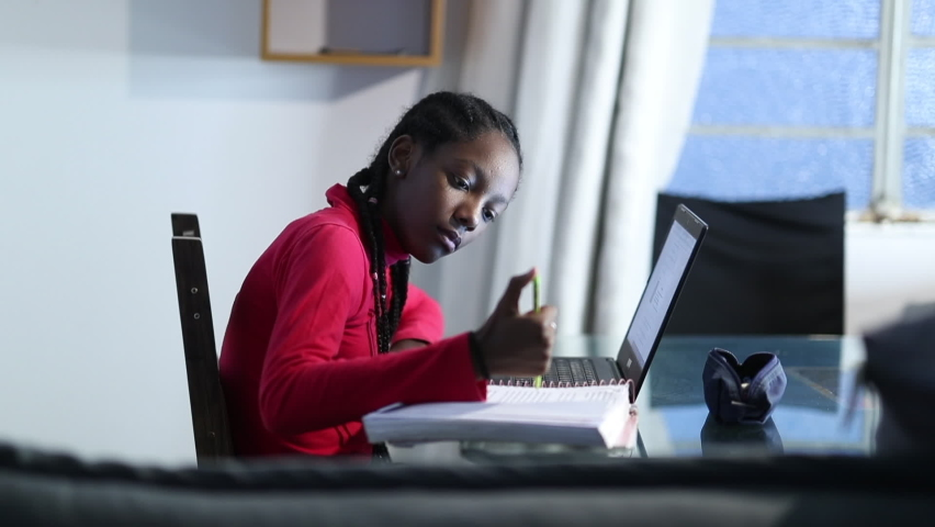 African girl taking notes studying at home in front of laptop computer. Royalty-Free Stock Footage #1062893566