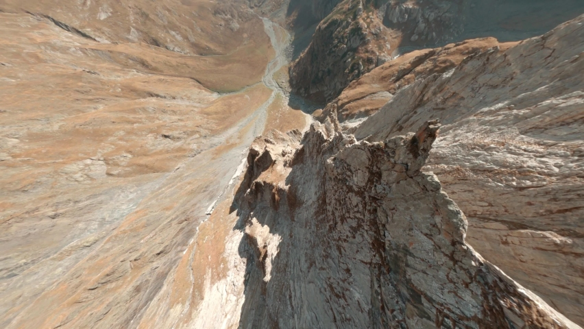 Fast extreme close diving drop down fly steep rocky mountain rock peak slopes and picturesque stone canyon with narrow winding creek on sunny day fpv racing drone first point aerial cinematic view.