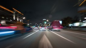 Amazing motion timelapse of the night rush drive in a big city. Speedy car driving the highway with a lot of lights and traffic, overtaking other vehicles and passing by skyscrapers along the road.